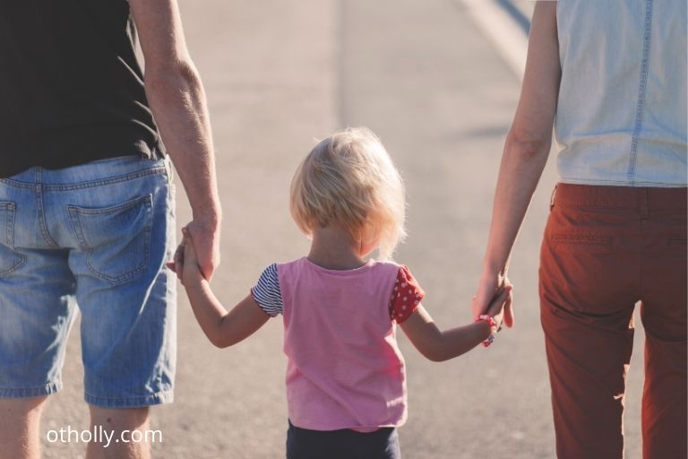toddler holding parents hands while walking