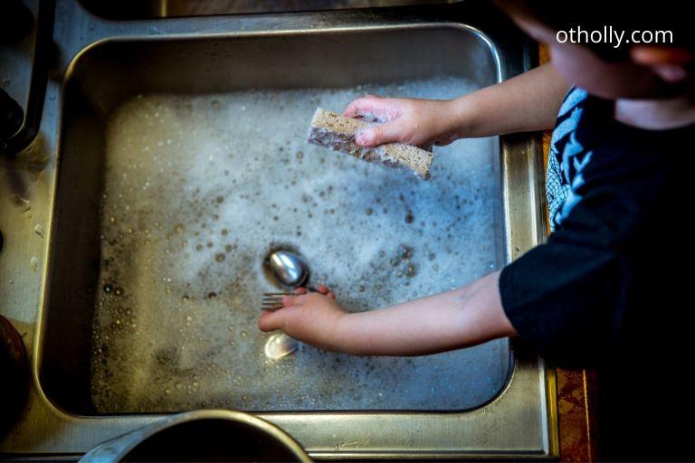 toddler washing dishes