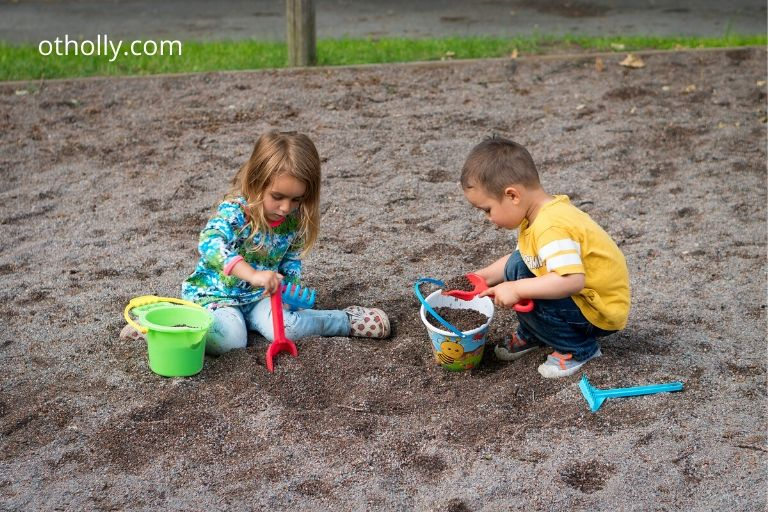 toddlers play in sand pit