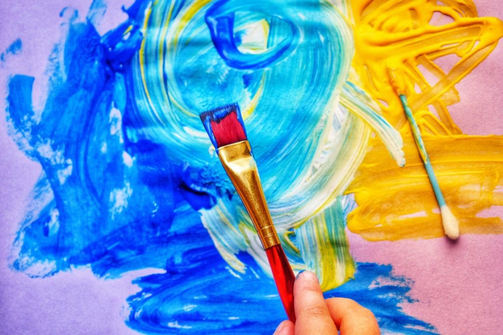 Picture of a toddler painting to represent the benefits of painting for toddlers development