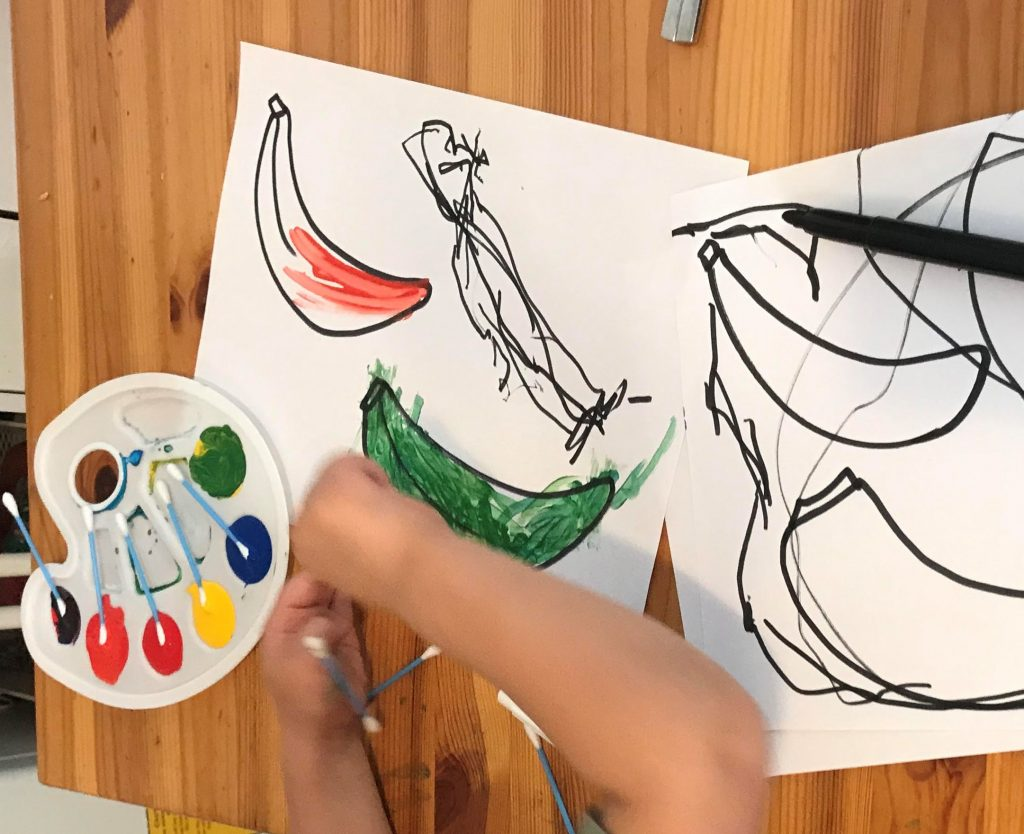 Picture of toddler painting self drawn bananas to show how painting boosts toddler development