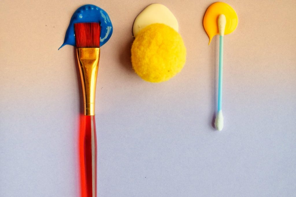 Picture of paint brush, q tip and pom pom to represent different paintbrushes toddlers can use